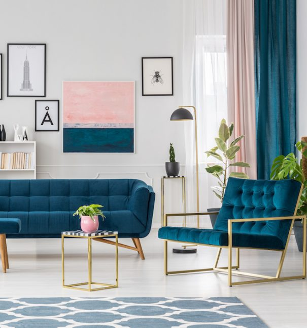Modern living room interior with blue sofa and armchair, patterned rug and posters on the wall